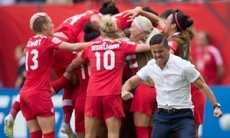 Canada coach John Herdman, right, celebrates as Josee Belanger, back, is mobbed by her team-mates after scoring against Switzerland in Vancouver.