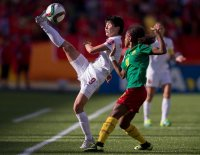 China's Wang Shanshan tries to keep the ball in play as she is pressured by Cameroon's Jeannette Yango during the FIFA Women's World Cup Group of 16 Match at Commonwealth Stadium in Edmonton, Canada on June 20, 2015