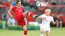 EDMONTON, AB - JUNE 11: Christine Sinclair (L) of Canada kicks the ball in front of Betsy Hassett of New Zealand during the FIFA Women's World Cup Canada Group A match between Canada and New Zealand at Commonwealth Stadium on June 11, 2015 in Edmonton, Alberta, Canada. (Photo by Todd Korol/Getty Images)