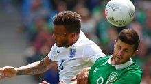 Ryan Bertrand of England competes for possession against Shane Long of Ireland.