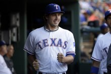 Texas Rangers' Derek Holland does a dance move in the dugout before a baseball game against the Houston Astros, Tuesday, Sept. 23, 2014, in Arlington, Texas. (AP Photo/Tony Gutierrez)